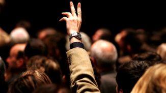 Tłum ludzi i wyciągnięta ręka ponad głowami