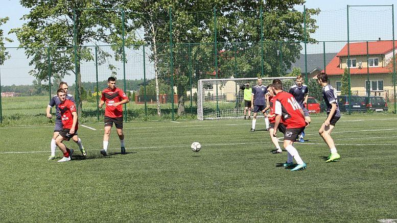 Piłkarze w czerwonych strojach podczas akcji przy piłce