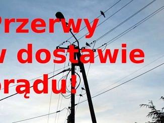 Lampa uliczna na tle nieba i czerwony napis przerwy w dostawie prądu