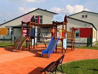 Przedszkole w Bujnach kolorowe zjeżdżalnie na tle budynków przedszkola