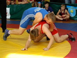 Dwaj młodzi zapaśnicy - w niebieskim i czerwonym stroju - siłują się na żółtej macie