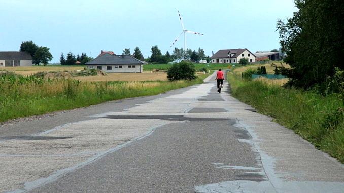 Droga asfaltowa, w oddali zabudowania