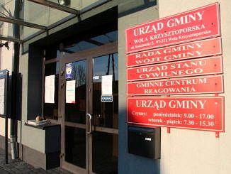 Wejście do budynku Urzędu Gminy. Na pierwszym planie czerwone tablice informacyjne
