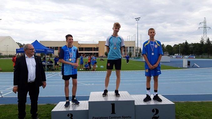 Zawodnicy na podium w towarzystwie Marka Mazura - Na najwyższym stopniu podium Piotr Kulka - zwycięzca biegu na 1000 m