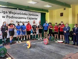 Uczestnicy Ligi Wojewódzkiej Juniorów w podnoszeniu ciężarów w Radomsku stoją w maseczkach, przed nimi sztanga