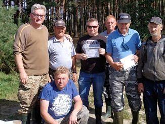 Uczestnicy zawodów o tytuł mistrza Koła nr 35 PZW z Woli Krzysztoporskiej metodą spławikową przy Zbiorniku Cieszanowice na tle drzew