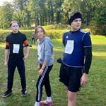 Młodzi biegacze dwaj chłopcy a pośrodku dziewczyna