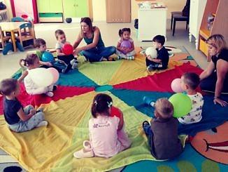 Dzieci z wychowawczynią siedzą na wielokolorowej, okrągłej płachcie