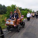 Dożynki Parafialne w Parzniewicach orgnizowane przez wsie Łużyk i Przydztki - przystrojona bryczka ciągnięta przez kucyka - jedzie nią mężczyzna w kapeluszu i chłopiec; w tyle procesja na czele z księdzem