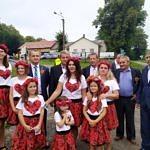 Grupa kobiet i dziewczynek ubrana na ludowo - czerwone, wzorzyste spódnice, czerwone wianki na głowach, białe koszulki z czerwonymi sercami