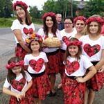 Grupa kobiet i dziewczynek ubrana na ludowo - czerwone, wzorzyste spódnice, czerwone wianki na głowach, białe koszulki z czerwonymi sercami - kobiety trzymają chleb dożynkowy