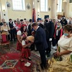 Kościół - wójt Roman Drozdek odbiera z rąk małej dziewczynki chleb dożynkowy