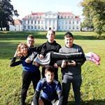 Grupa biegaczy z Bujen na tle szkoły (pałacu) w Wolborzu - trzej chłopcy trzymaja na rękach dziewczynę, jeden kuca