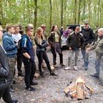 Grupa młodzieży stoi przy ognisku