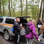Młodzi ludzie przy samochodzie z materiałami do zbierania śmieci