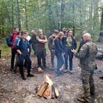 Uczniowie ZS CKZ Bujny stoją przy ognisku - słuchają mówiącego przedstawiciel Lasów Państwowych