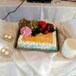 Tort z kolorowym, kwiatowym przybraniem, obok świeczki