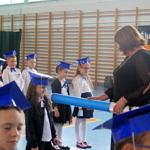Dyrektor szkoły mianuje pierszaków wielkim niebieskim ołówkiem na uczniów