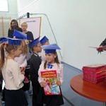 Dyrektor szkoły wraz z wychowawcami wręcza dzieciom pamiątkowe książki