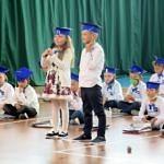 Grupa pierwszaków podczas występów artystycznych - ubrani na galowo w niebieskich czapkach - dziewczynka i chłopiec stoją z mikrofonem, reszta siedzi na podłodze