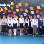 Klasa pierwsza z wychowawcą - dzieci stoją w rzędzie na tle dekoracji z liści z napisem ślubujemy