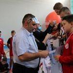 Mistrzostwa Polski Szkół Podstawowych U15 w zapasach w stylu klasycznym - zawodnicy na podium, medale i koszulki wręcza Tomasz Woźniak