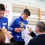Mistrzostwa Polski Szkół Podstawowych U15 w zapasach w stylu klasycznym - zawodnicy na podium otrzyują medale i koszulki