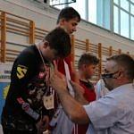 Mistrzostwa Polski Szkół Podstawowych U15 w zapasach w stylu klasycznym - zawodnicy na podium dekorowni medalami przez Tomasza Woźniaka