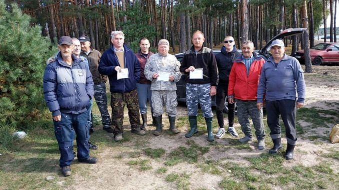 Grupa wędkarzy nad zbiornikie Cieszanowice na tle lasu; zwycięzcy z dyplomami