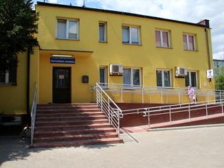 Óśrodek zdrowia w Woli Krzysztoporskiej - żółty budynek ze schodami i podjazdem dla niepełnosprawnych