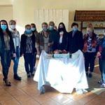 Członkinie KGW Piekarzanki stoją w maseczkach - przed nimi na stoliku tort
