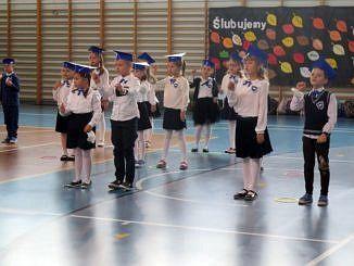 Grupa pierwszaków podczas występów artystycznych - ubrani na galowo w niebieskich czapkach