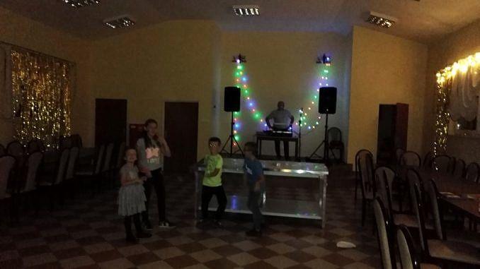 Wnetrze sali w Domu Ludowym w Woli Rokszyckiej - czworo dzieci stoi przy nowym sprzęcie nagłaśniającym; za mimi na poswyższonej scenie mężczyzna przy stoje didżejskim