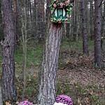Mała kapliczka umieszczona na drzewie ozdobiona chryzantemami w doniczkach