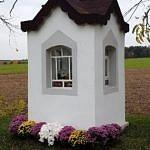 Biała, murowana kapliczka ozdobiona chryzantemami w doniczkach