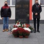 Sołtys Borowej Artur Jedrzejczyk i sołtys Parzniewiczek Adam zajączkowski stoją przy pomniku przed Urzędem Gminy w Woli krzysztoporskiej. Przed pomnikiem leżą biało-czerwone wieńce i stoją białe i czerwone chryzantemy w doniczkach