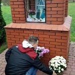 Sołtys Borowej Artur Jędrzejczyk stawi kwiaty przed kapliczką