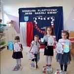 Grupa przedszkolaków prezentuje wykonane własnoręcznie herby gminy Wola Krzysztoporska