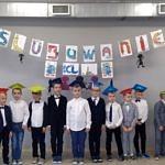Dzieci w strojach galowych i czapkach stoją w rzędzie; u góry napis ślubowanie