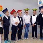 Dzieci w strojach galowych i czapkach stoją w rzędzie;