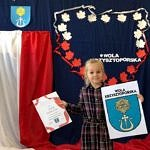 Dziewczynka prezentuje wykonany własnoręcznie herb gminy Wola Krzysztoporska