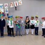 Dzieci w strojach galowych i czapkach, z papierowymi kwiatami w rękach stoją w rzędzie; u góry napis ślubowanie