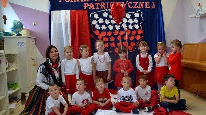 """Przedszkolaki prezentują się w biało-czerwonych strojach. Na ścianie na granatowym tle napis """"Pokaz mody patriotycznej"""", poniżej kształt Polski wypełniony biało-czerwonymi liśćmi, obok biało-czerwona flaga. Grupa przedszkolna z opiekunką w ludowym stroju"""