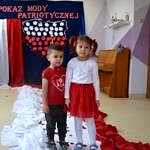 """Przedszkolaki prezentują sie w biało-czerwonych strojach. Na ścianie na granatowym tle napis """"Pokaz mody patriotycznej"""", poniżej kształt Polski wypełniony biało-czerwonymi liśćmi, obok biało-czerwona flaga. Przedszkolaki chodzą po biało-czewonym podeście - dywanie"""