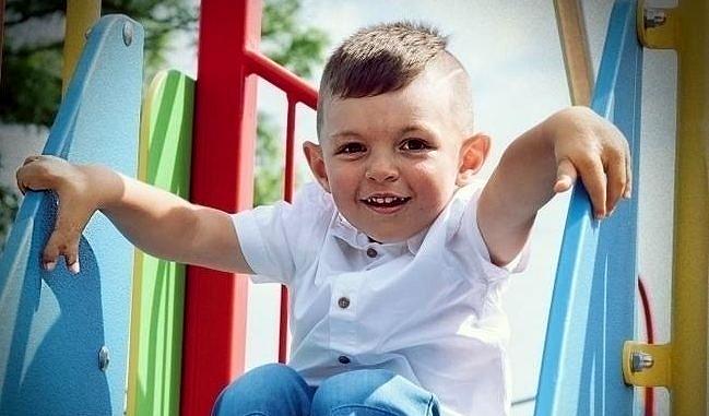 Uśmiechnięty chłopiec na zjeżdżalni - widoczne deformacje dłoni