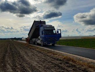 Nowa droga asfaltowa, obok zaorane pole, na niej samochód ciężarowy wykonujący prace drogowe wszystko na tle pokrytego chmurami nieba