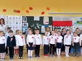 Maluchy ubrane w galowe stroje z kotylionami śpiewają hymn narodowy