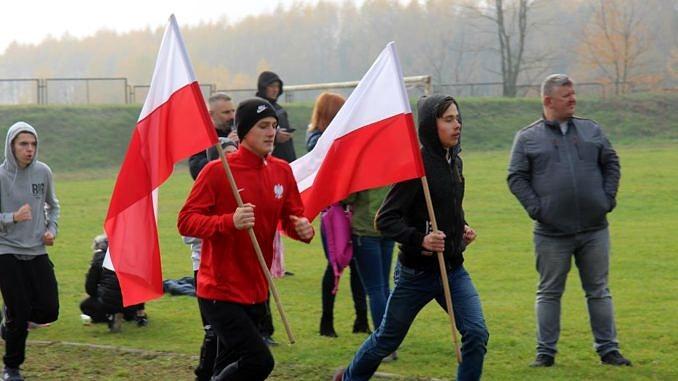 Biegacze z biało-czerwonymi flagami