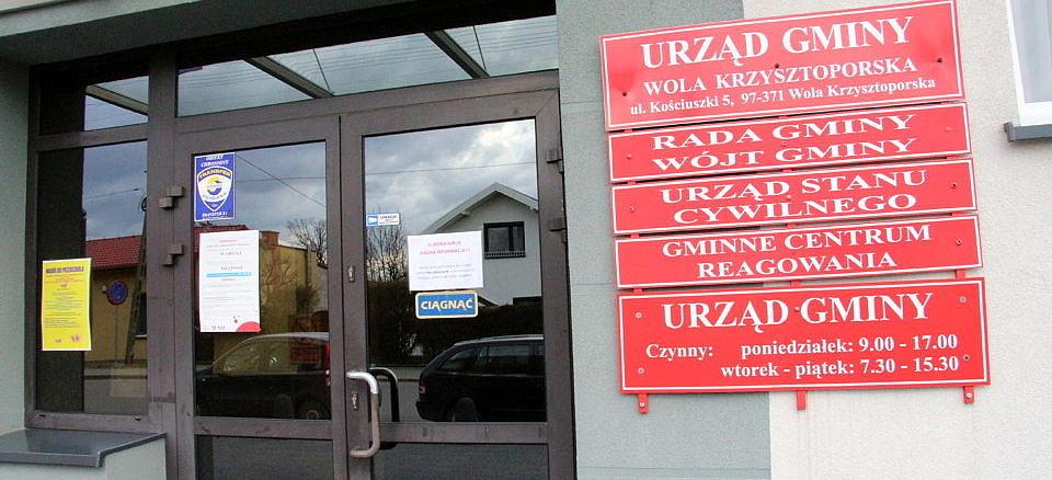 Drzwi do Urzędu Gminy w Woli Krzysztoporskiej, obok czerwone tablice informacyjne