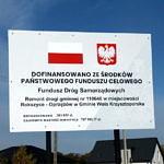 Tablica informacyjna o dofinansowaniu przebudowy drogi Rokszyce - Oprzężów ze środków Panstwowego Funduszu Celowego - Funduszu Dróg Samorządowych